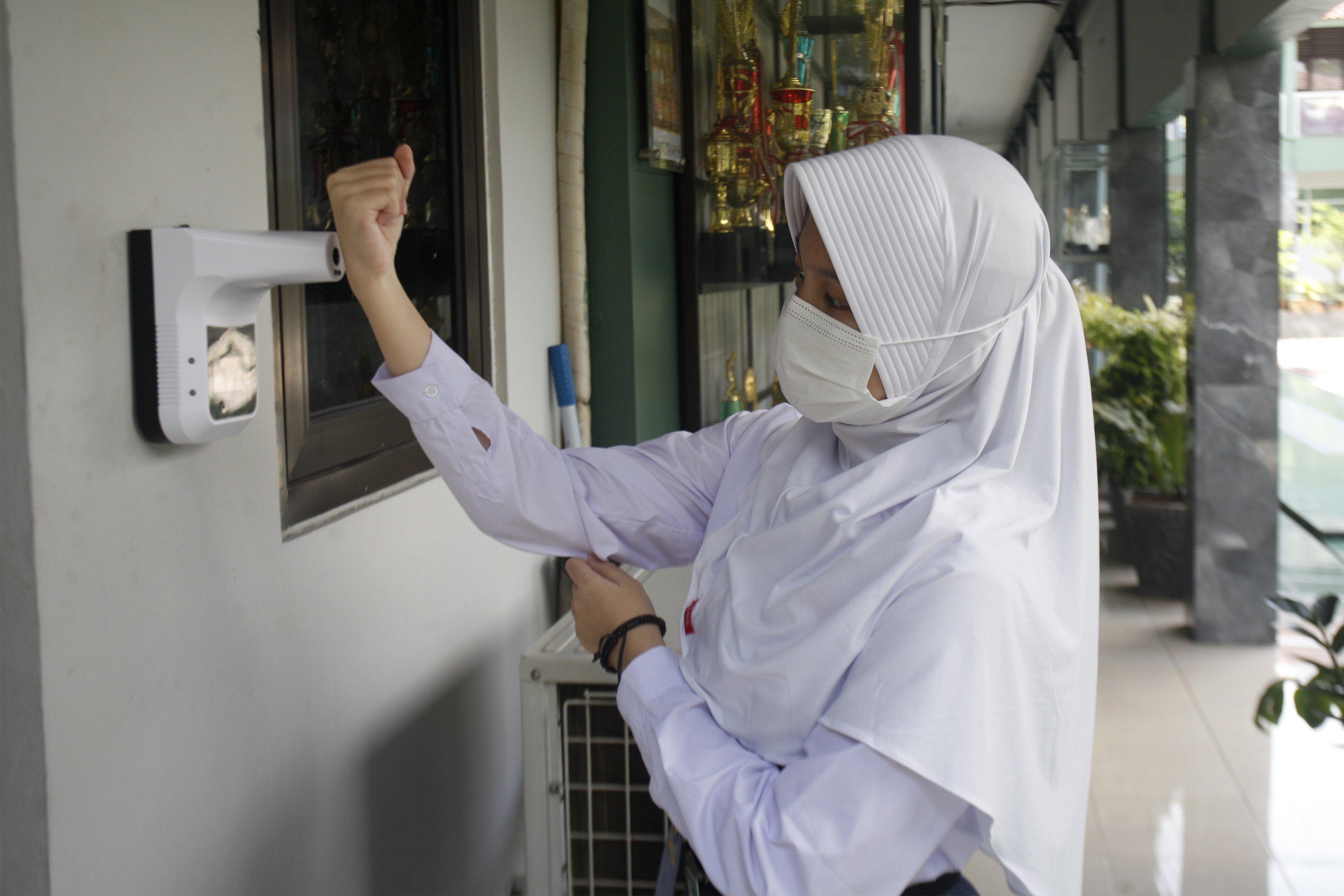 Siswa mengecek suhu tubuh sebelum masuk kelas saat kegiatan uji coba belajar mengajar tatap muka dengan menerapkan protokol kesehatan di SMAN 2 Cibinong, Kabupaten Bogor, Jawa Barat, Senin (15/3/2021). ?Sebanyak 170 sekolah di Kabupaten Bogor, Jawa Barat, mulai menggelar uji coba pembelajaran secara tatap muka mulai hari ini hingga 10 April 2021, dari jumlah 232 sekolah yang diusulkan hasil verifikasi dan validasi yang lolos berjumlah 170 sekolah.