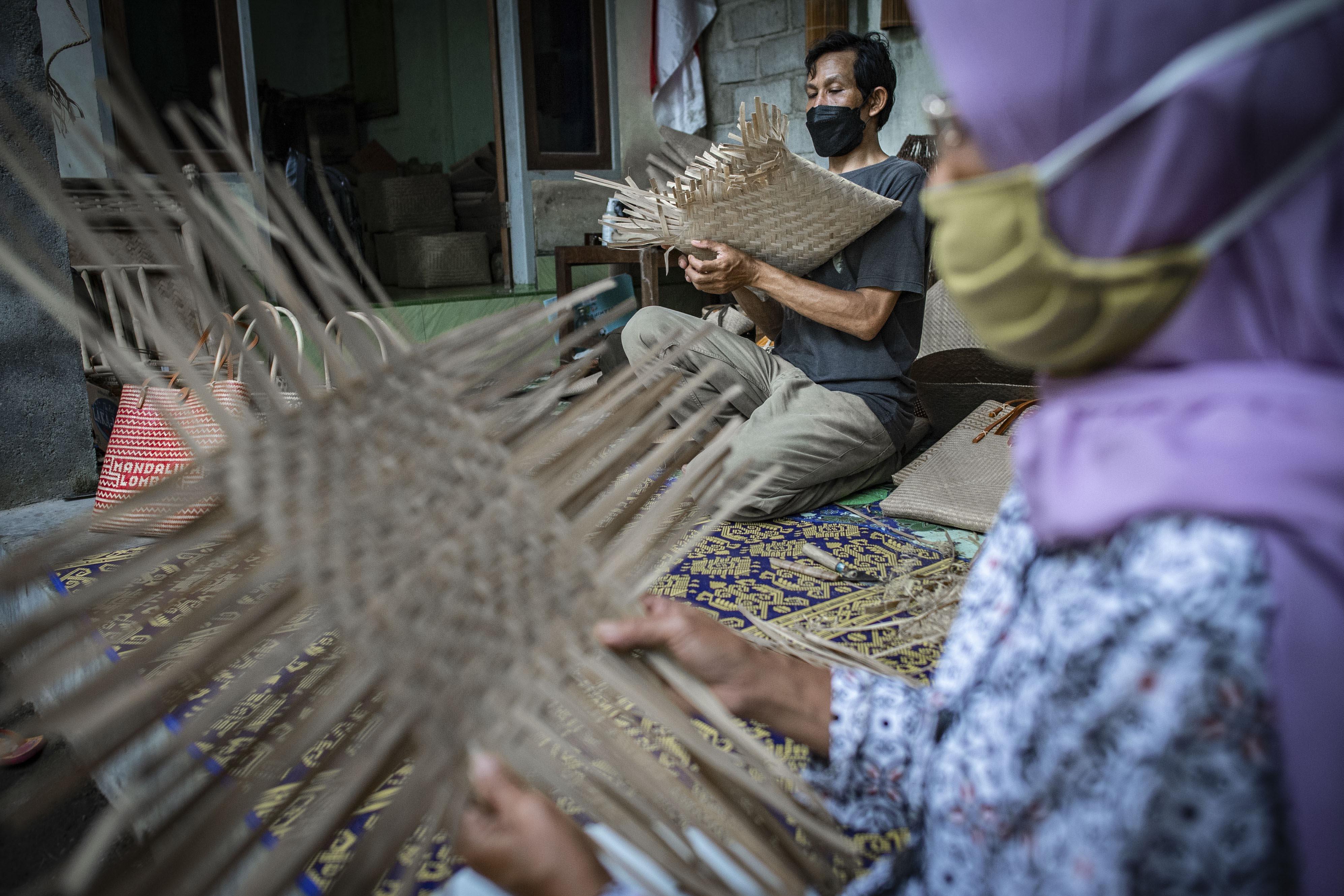 Agus Hartadi (kiri) bersama pengrajin setempat menyelesaikan anyaman bambu di Desa Loyok, Sakra, Lombok Timur, Nusa Tenggara Barat.