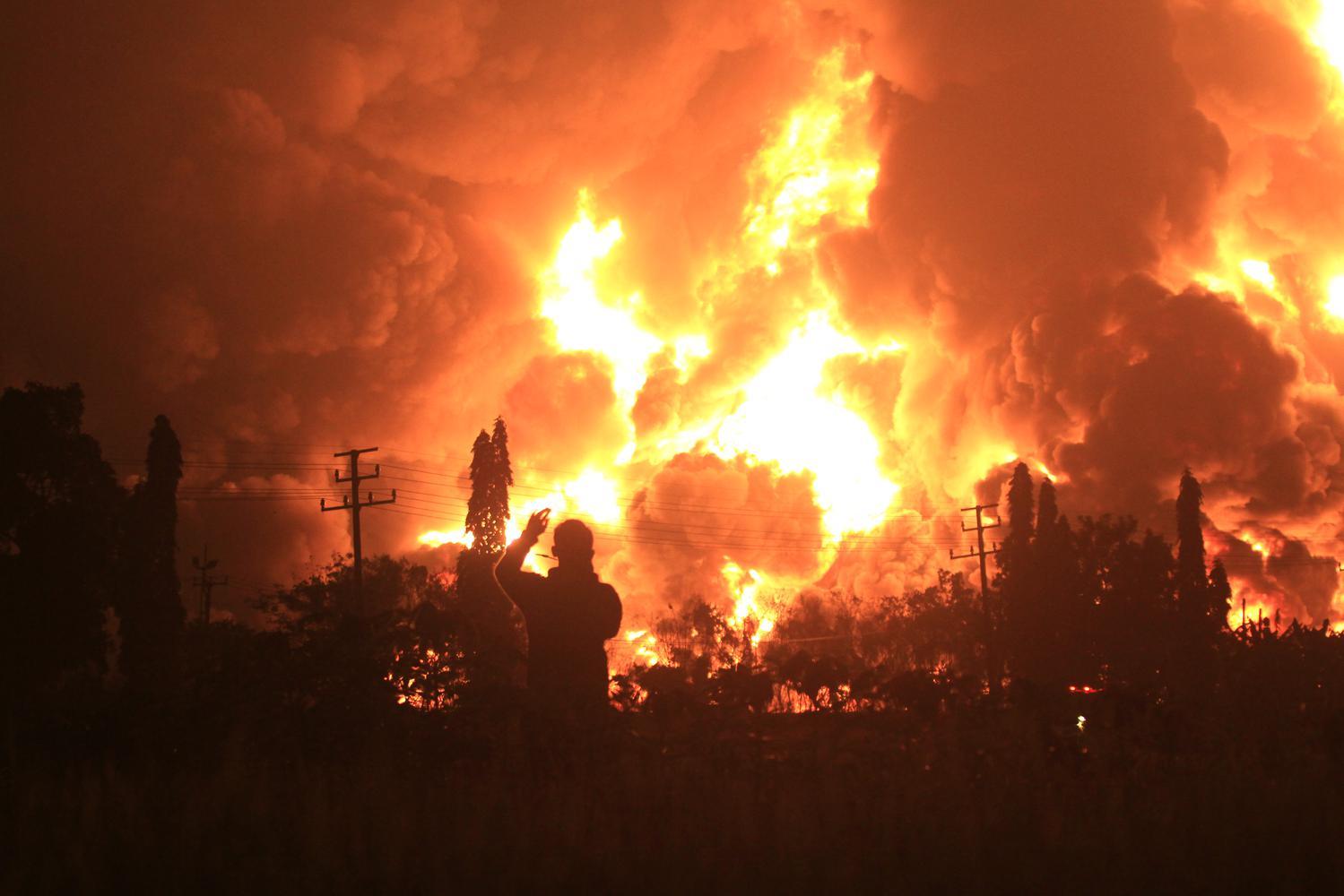 Warga mengambil video dengan gawai miliknya saat terjadi kebakaran di kompleks Pertamina RU VI Balongan, Indramayu, Jawa Barat, Senin (29/3/2021) dini hari.