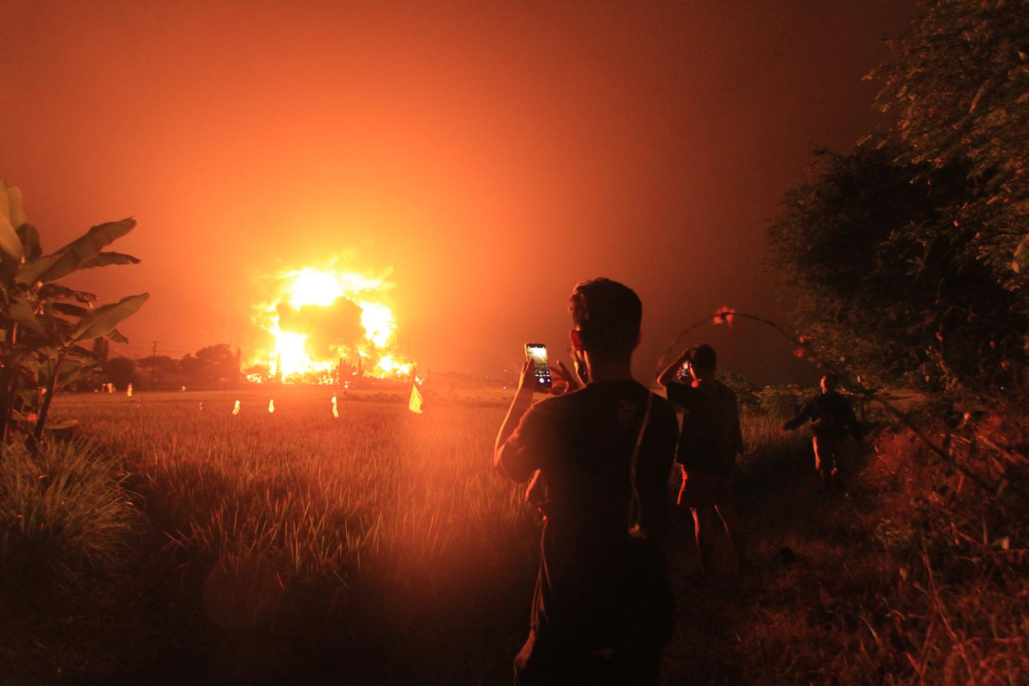 Warga menyaksikan kebakaran di kompleks Pertamina RU VI Balongan, Indramayu, Jawa Barat, Senin (29/3/2021) dini hari.