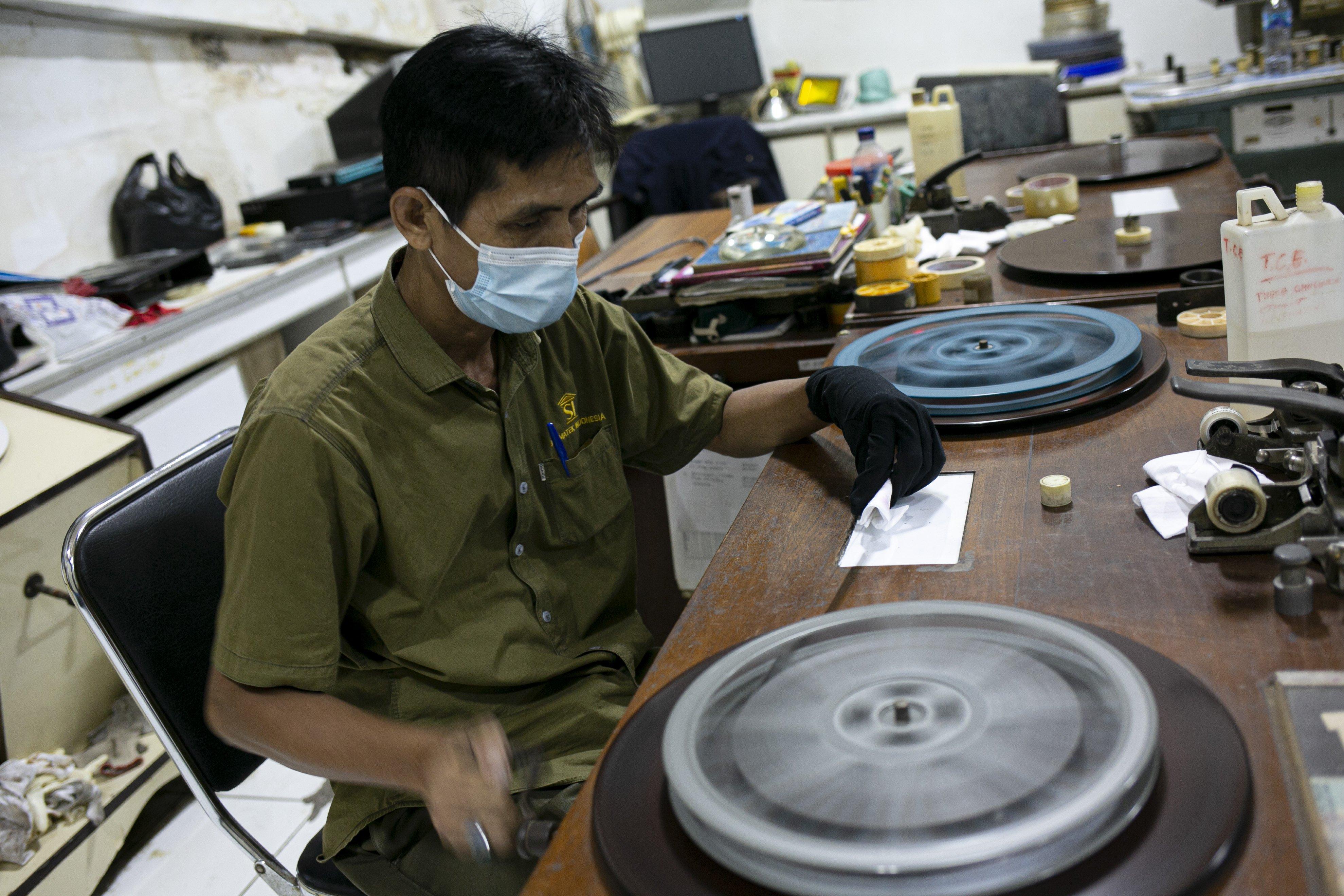 Firdaus (50), membersihkan gulungan seluloid di Gedung Sinematek, jalan HR. Rasuna Said, RT.2/RW.5, Karet Kuningan, Kecamatan Setiabudi, Kota Jakarta Selatan.