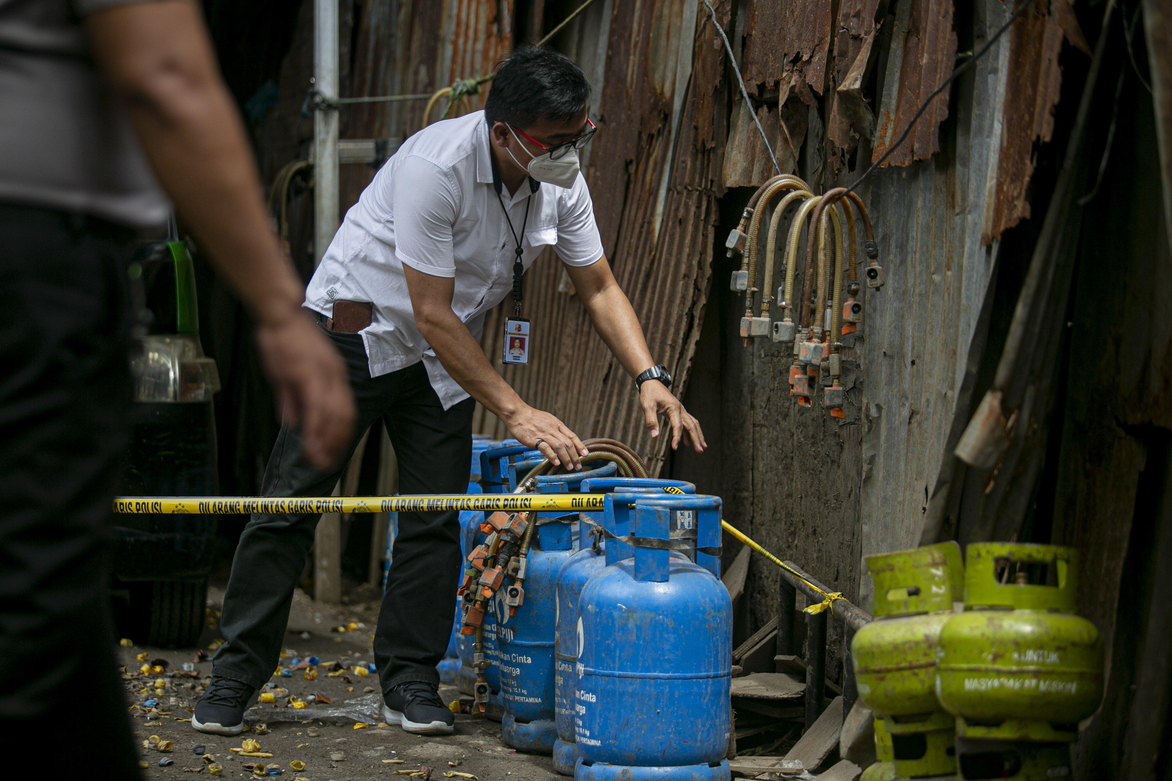 Petugas memeriksa barang bukti tabung gas LPG kasus pengoplosan gas bersubsidi di kawasan Meruya, Jakarta Barat, Selasa (6/4/2021). Bareskrim Polri membongkar praktik kecurangan dengan cara menyalahgunakan penggunaan gas LPG subsidi 3 kg dengan menyuntikkan ke gas 12 kg, aksi tersebut berlangsung sejak tahun 2018 dengan kerugian negara mencapai Rp 7 miliar.