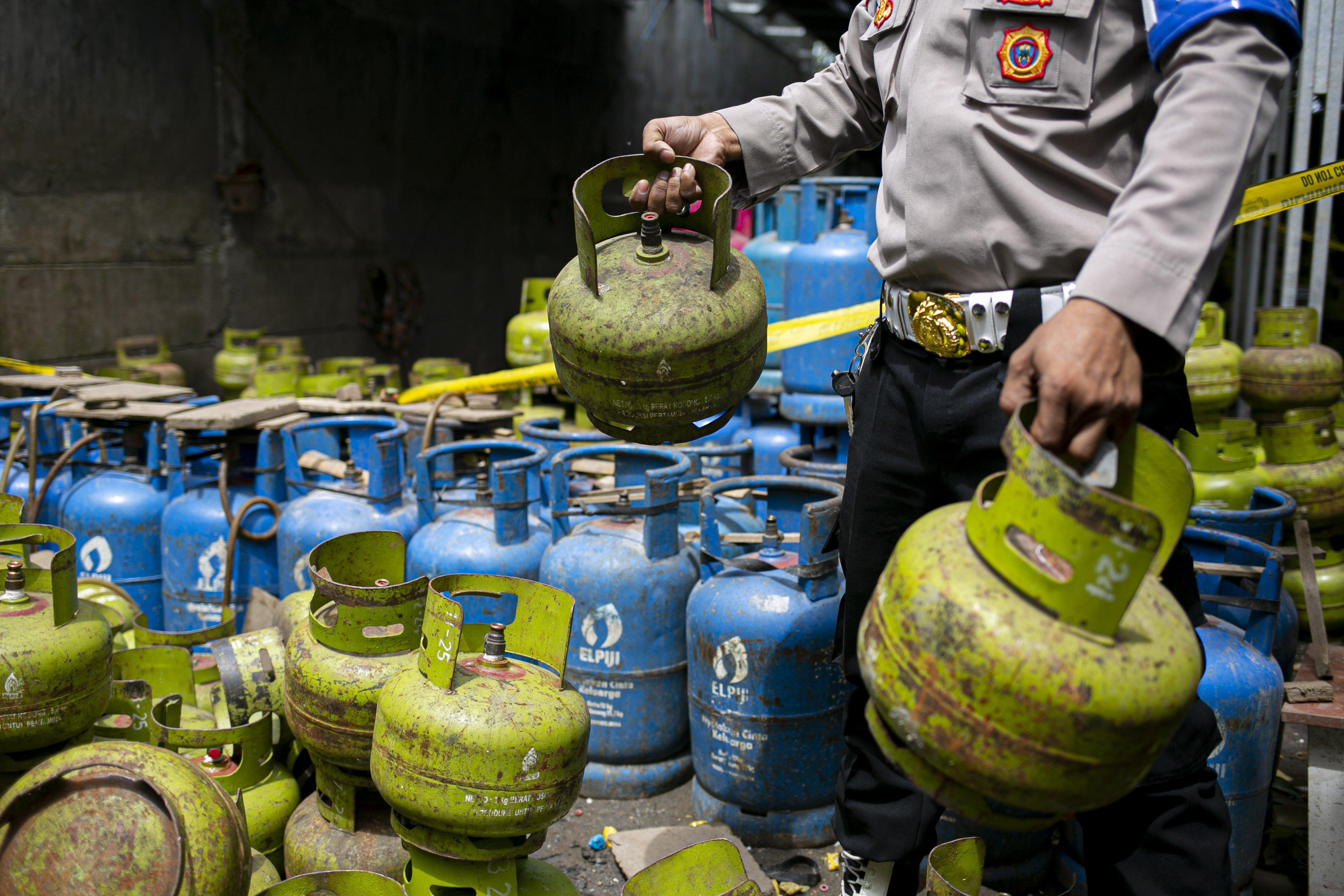 Petugas menunjukan barang bukti tabung gas LPG kasus pengoplosan gas bersubsidi di kawasan Meruya, Jakarta Barat, Selasa (6/4/2021). Bareskrim Polri membongkar praktik kecurangan dengan cara menyalahgunakan penggunaan gas LPG subsidi 3 kg dengan menyuntikkan ke gas 12 kg, aksi tersebut berlangsung sejak tahun 2018 dengan kerugian negara mencapai Rp 7 miliar.