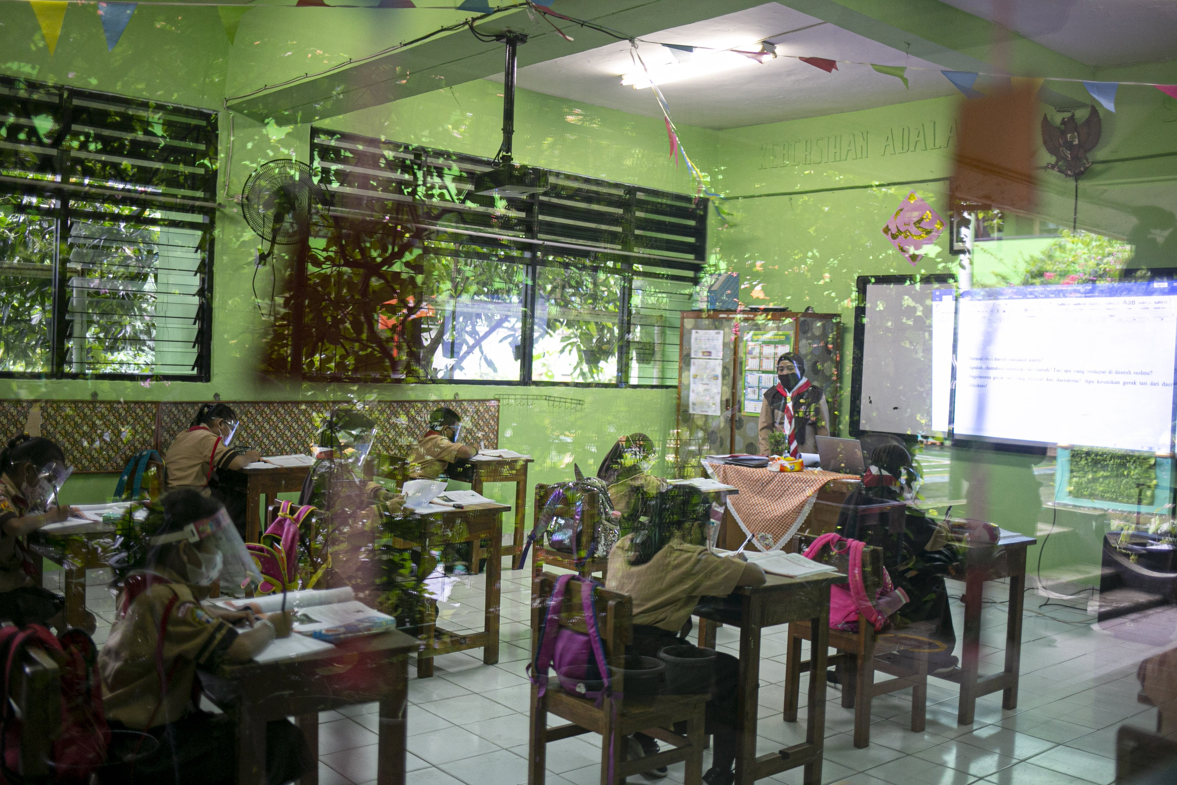 Sejumlah siswa mengikuti uji coba pembelajaran tatap muka di SDN Kenari 08 pagi, Jakarta, Rabu (7/4/2021). Pemerintah Provinsi DKI akan melakukan uji coba pembelajaran tatap muka terbatas di 85 sekolah mulai 7 April hingga 29 April 2021 dengan menerapkan protokol kesehatan Covid-19 yang ketat. Skema yang akan diterapkan adalah pembelajaran tatap muka secara bergantian di dalam ruangan maksimum 50 persen dari kapasitas ruangan.