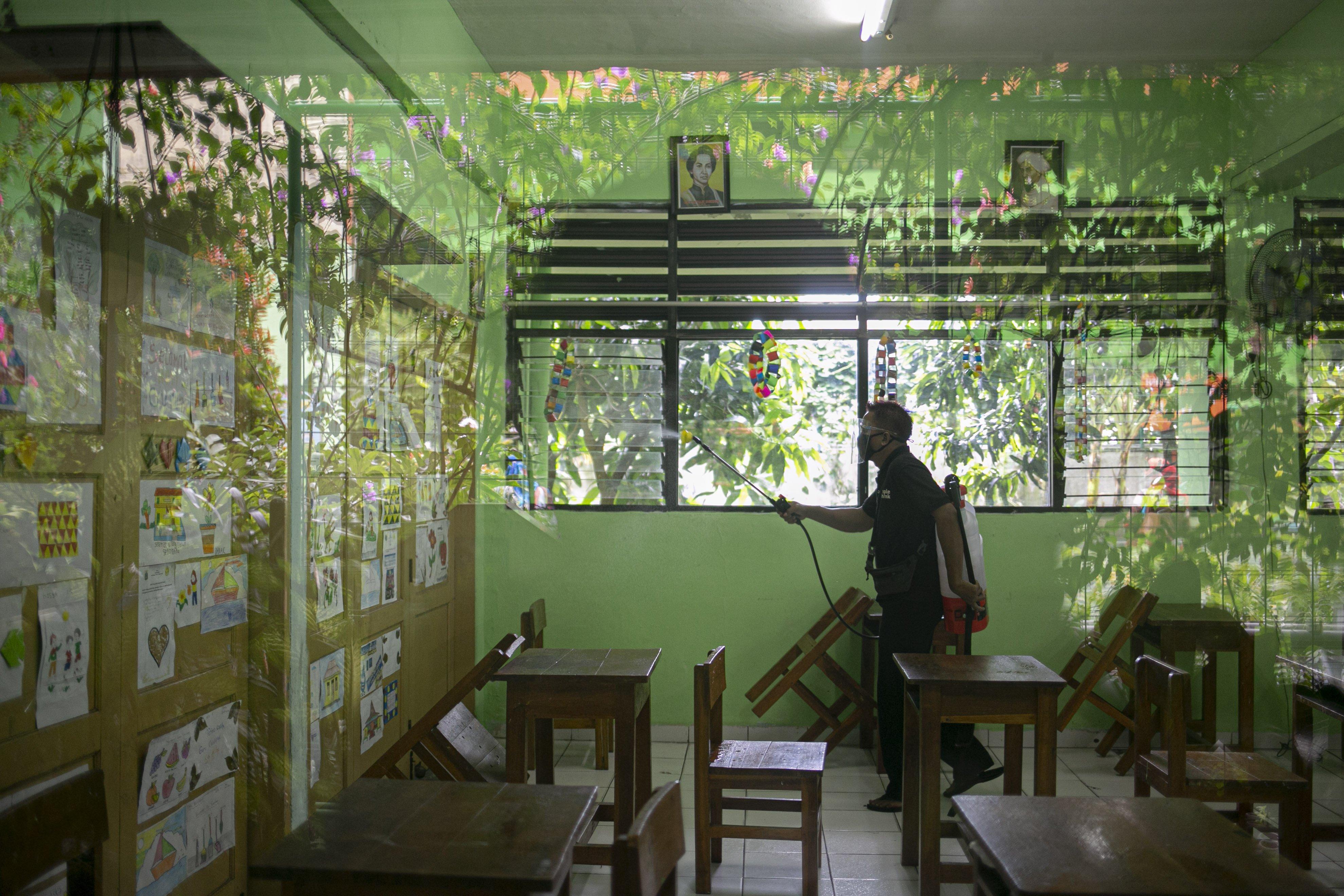 Petugas menyemprotkan cairan disinfektan seblum melaksanakan pembelajaran tatap muka di SDN Kenari 08 pagi, Jakarta, Rabu (7/4/2021). Pemerintah Provinsi DKI akan melakukan uji coba pembelajaran tatap muka terbatas di 85 sekolah mulai 7 April hingga 29 April 2021 dengan menerapkan protokol kesehatan Covid-19 yang ketat. Skema yang akan diterapkan adalah pembelajaran tatap muka secara bergantian di dalam ruangan maksimum 50 persen dari kapasitas ruangan.