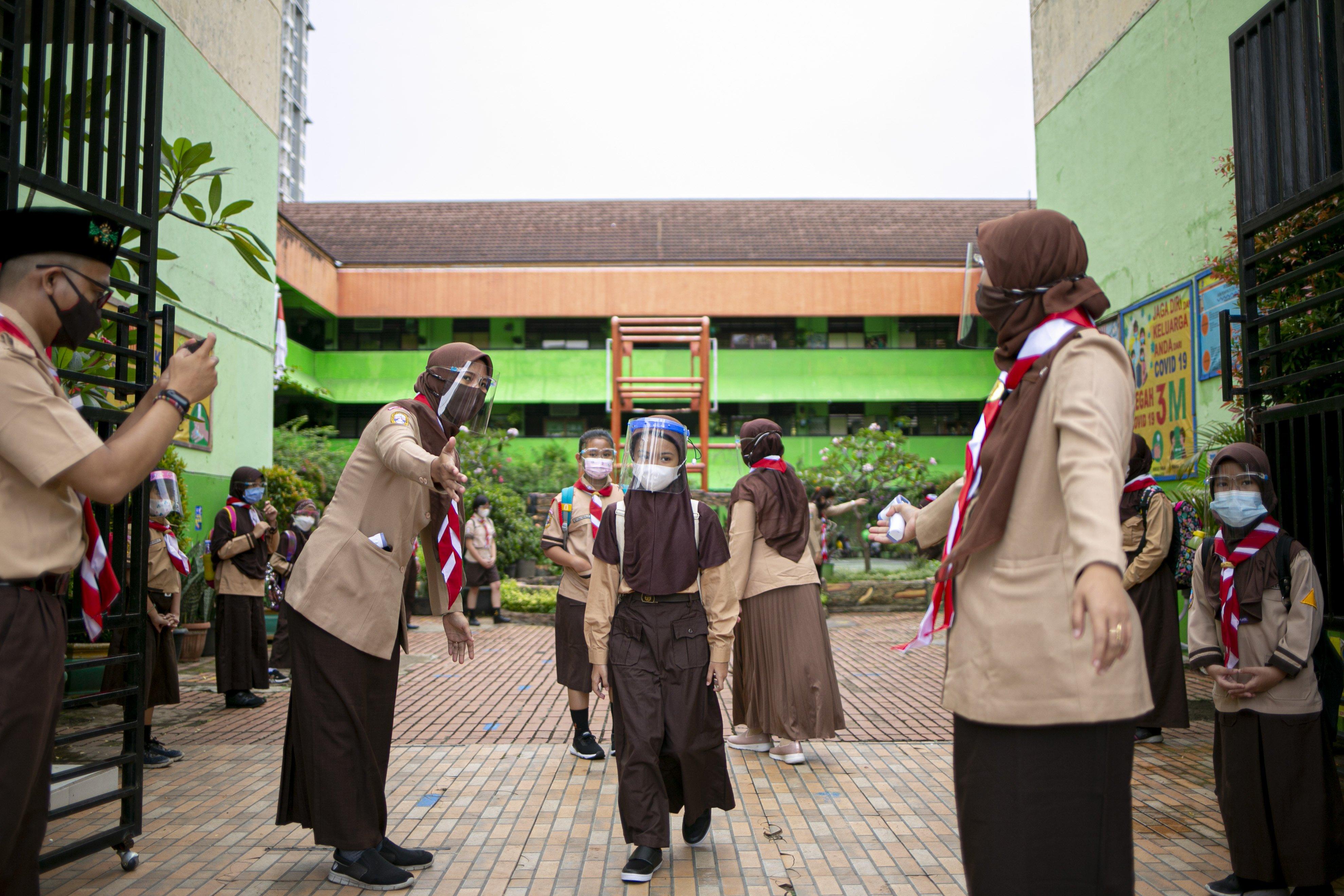 Siswa keluar sekolah usai mengikuti uji coba pembelajaran tatap muka di SDN Kenari 08 pagi, Jakarta, Rabu (7/4/2021). Pemerintah Provinsi DKI akan melakukan uji coba pembelajaran tatap muka terbatas di 85 sekolah mulai 7 April hingga 29 April 2021 dengan menerapkan protokol kesehatan Covid-19 yang ketat. Skema yang akan diterapkan adalah pembelajaran tatap muka secara bergantian di dalam ruangan maksimum 50 persen dari kapasitas ruangan.