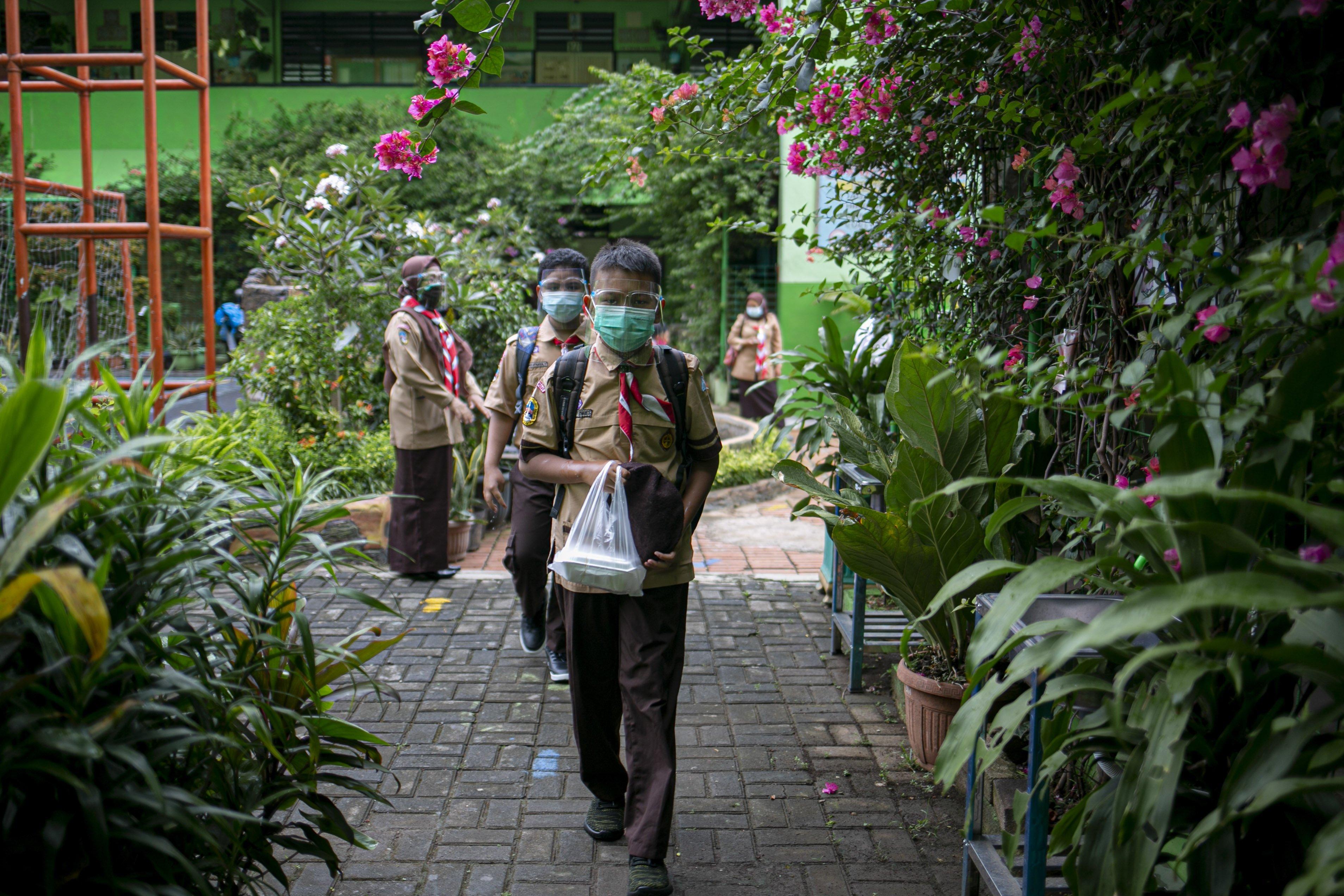 Sejumlah siswa memasuki sekolah untuk mengikuti uji coba pembelajaran tatap muka di SDN Kenari 08 pagi, Jakarta, Rabu (7/4/2021). Pemerintah Provinsi DKI akan melakukan uji coba pembelajaran tatap muka terbatas di 85 sekolah mulai 7 April hingga 29 April 2021 dengan menerapkan protokol kesehatan Covid-19 yang ketat. Skema yang akan diterapkan adalah pembelajaran tatap muka secara bergantian di dalam ruangan maksimum 50 persen dari kapasitas ruangan.