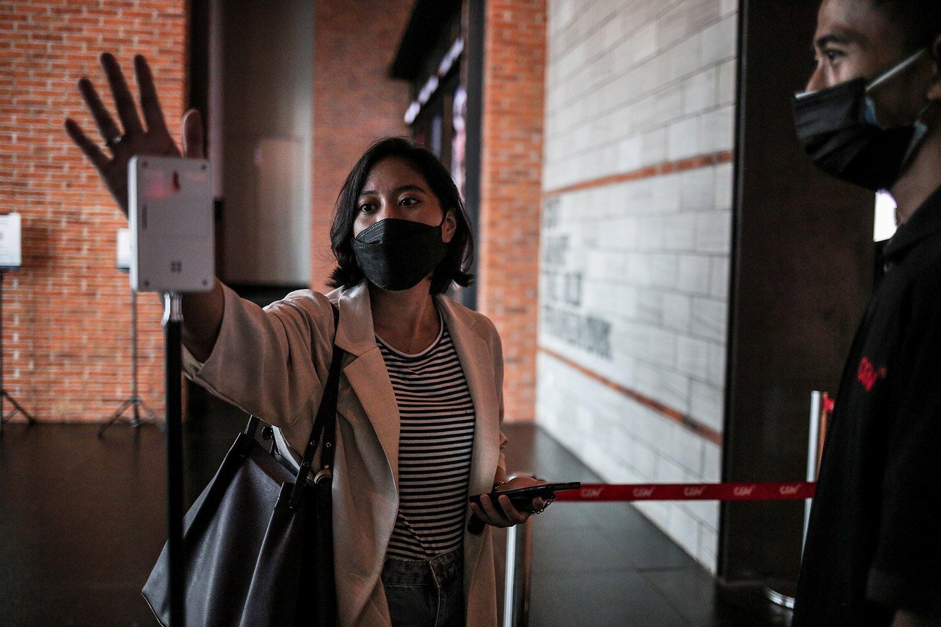 Pengunjung mengecek suhu badan menggunakan termometer saat hendak menonton di Bioskop CGV Grand Indonesia di Jakarta, Kamis (16/9/2021). Pemerintah memberikan kelonggaran dengan diperbolehkannya bioskop buka kembali di wilayah-wilayah dengan status pemberlakuan pembatasan kegiatan masyarakat (PPKM) level 3 dan 2 dengan kapasitas pengunjung 50 persen, penggunaan aplikasi PeduliLindungi, telah tervaksinasi COVID-19 dosis kesatu serta kedua dan menerapkan protokol kesehatan secara ketat.