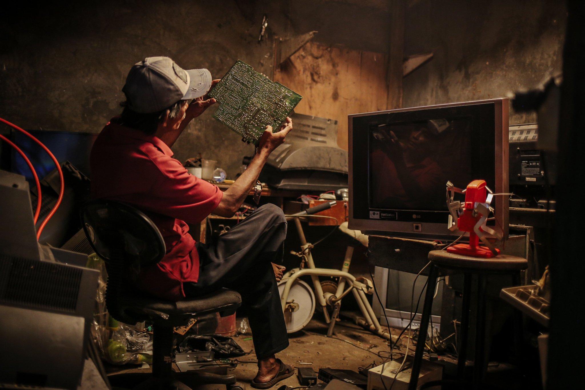 Pekerja mereparasi TV tabung di dalam ruang servis di Mal Rongsok Beji, Depok, Jawa Barat, Jumat, (17/9/2021).Untuk mengurangi peningkatan limbah eletronik Nurcholis Agi mengubahanya menjadi barang yang lebih bernilai dan bermanfaat.