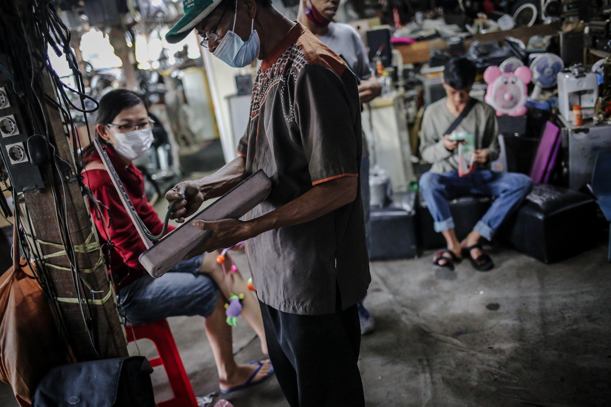 Pengunjung memilah barang bekas yang digantungkan di Mal Rongsok Beji, Depok, Jawa Barat, Jumat, (17/9/2021). Pengunjug yang datang ke Mal Rongsok tersebut tak hanya datang dari wilayah sekitar, namun hingga ke luar pulau, bahkan negara lain seperti Australia dan Jepang, untuk sekedar mencari barang-barang unik.