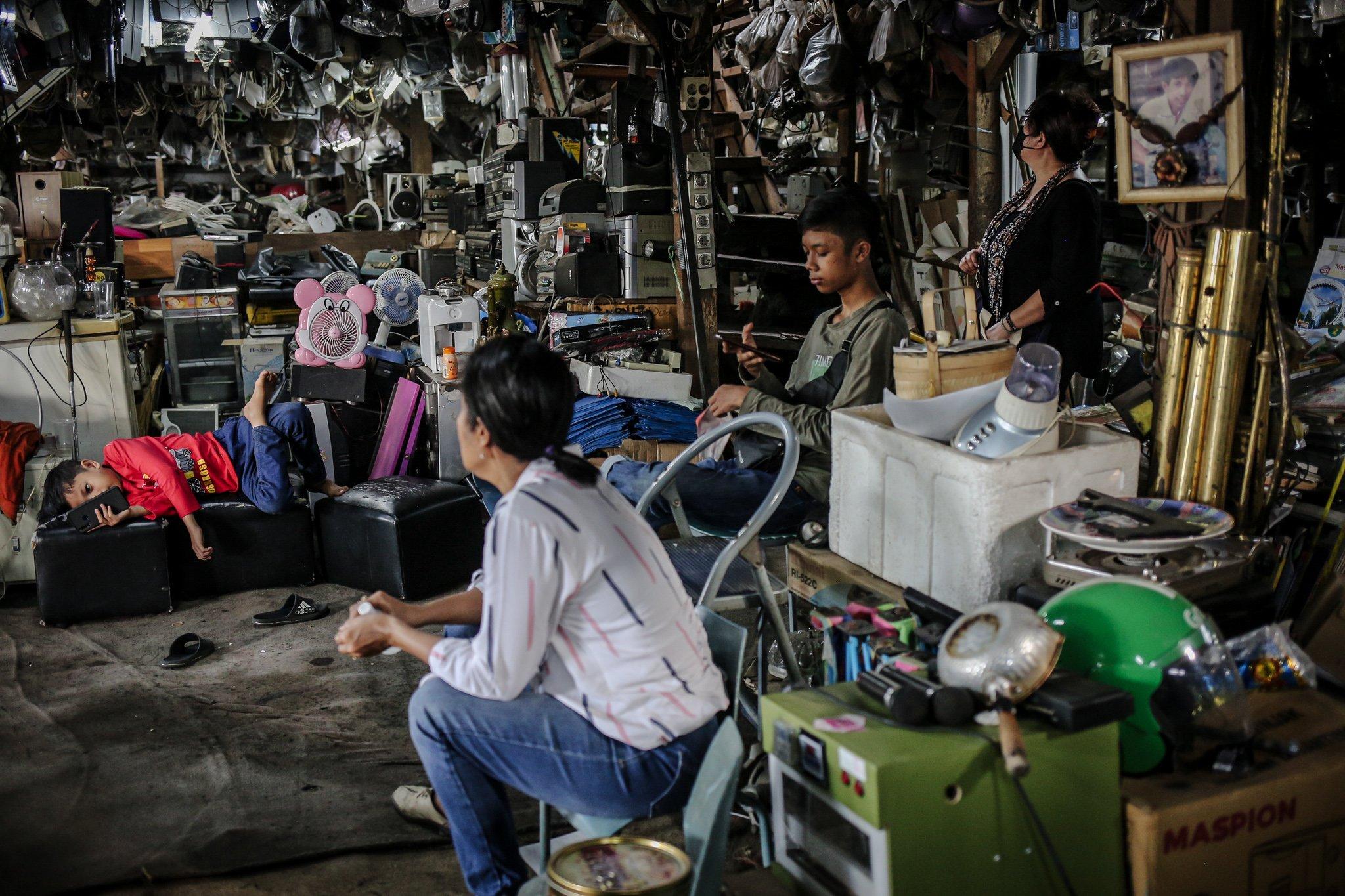 Pekerja menjaga barang-barang yang digantung di Mal Rongsok Beji, Depok, Jawa Barat, Jumat, (17/9/2021). Selama masa pandemi Covid-19, sekitar 82,9% pelaku UMKM alami penurunan omzet. pemilik Mal Rongsok itu juga mengaku demikian.