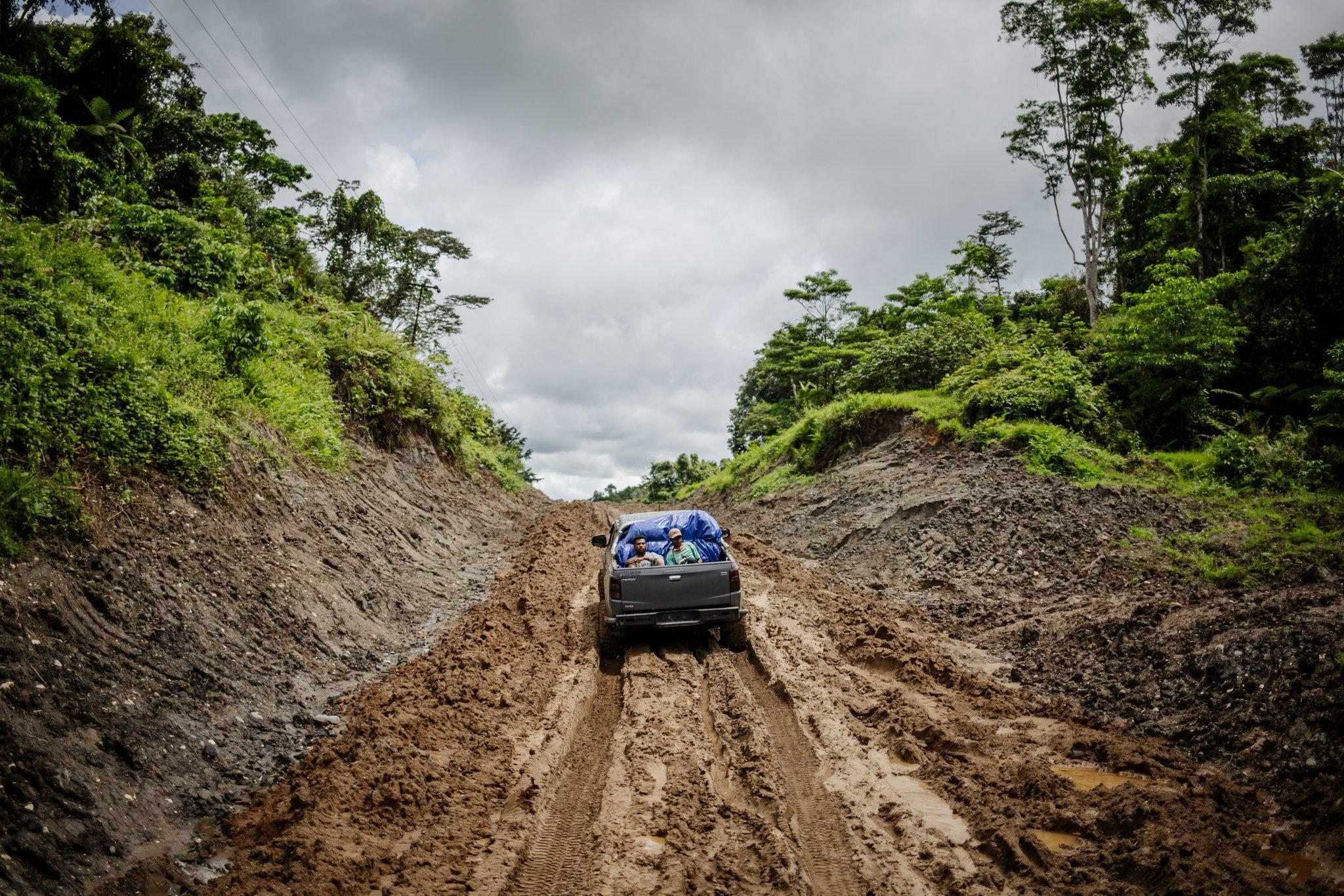 Sejumlah warga melintas jalan berlumpur di KM 17, satu-satunya jalan menuju Distrik Segun, Kabupaten Sorong, Papua Barat, Minggu, (19/9/2021). Banyaknya ativitas truk di wilayah perkebunan sawit membuat jalan-jalan di wilayah tersebut rusak dan berlumpur, sering kali warga bermalam di jalan ini untuk menunggu jalan kembali kering dan bisa dilintasi kendaraan bermotor.