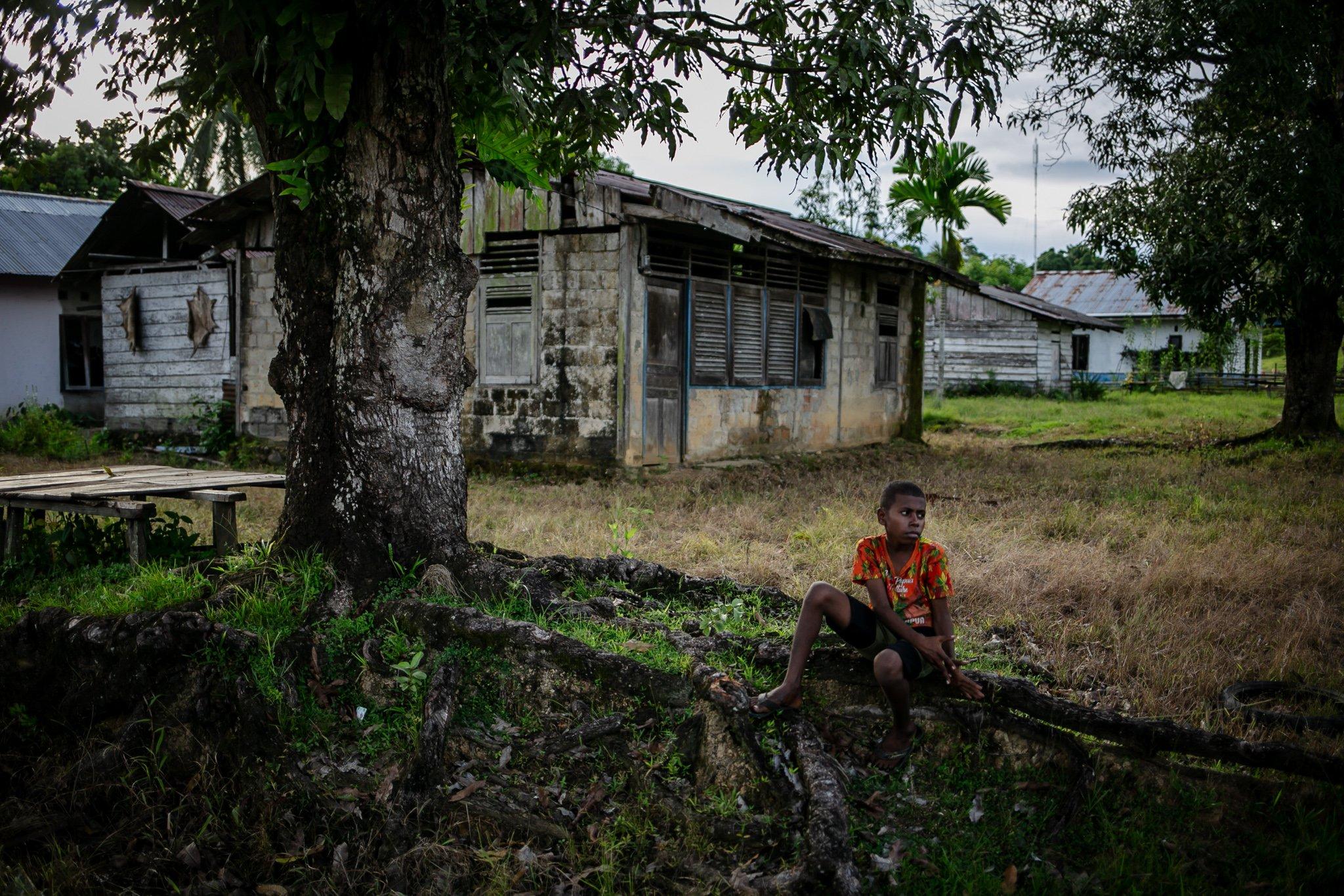 Sejumlah anak duduk di atas akar pohon di Distrik Segun, Kabupaten Sorong, Papua Barat, Minggu, (19/9/2021). Tak banyak anak remaja di kampung adat ini, sebagian besar anak-anak berusia 13-20 yang melanjutkan pendidikan tingkat menengah dan atas harus menginap di ditrik lain karena hanya sekolah dasar yang ada disana.