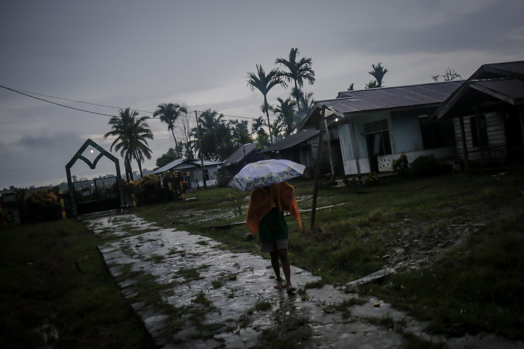 Sejumlah warga mennggunakan handuk dan payung berjalan di Distrik Segun, Kabupaten Sorong, Papua Barat, Minggu, (19/9/2021).