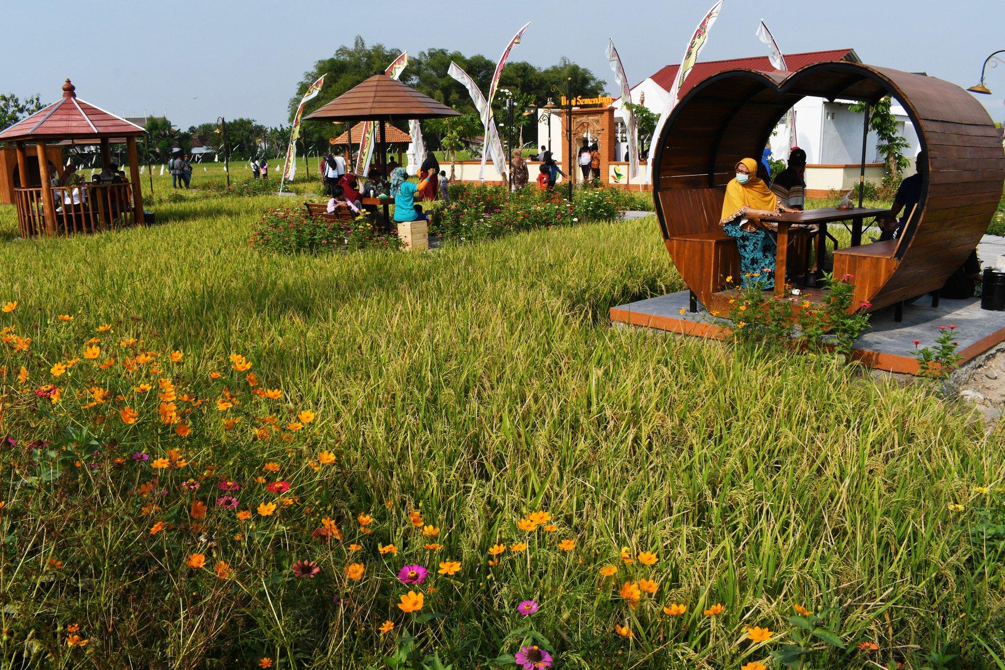 Pengunjung menikmati suasana objek wisata Lapak Bumi Semendung di Kelurahan Klegen, Kota Madiun, Jawa Timur, Minggu (26/9/2021). Pemkot Madiun membangun objek wisata dan lapak Usaha Mikro Kecil Menengah (UMKM) di areal persawahan tersebut untuk menarik wisatawan serta menumbuhkan perekonomian bagi warga setempat. ANTARA FOTO/Siswowidodo/foc.