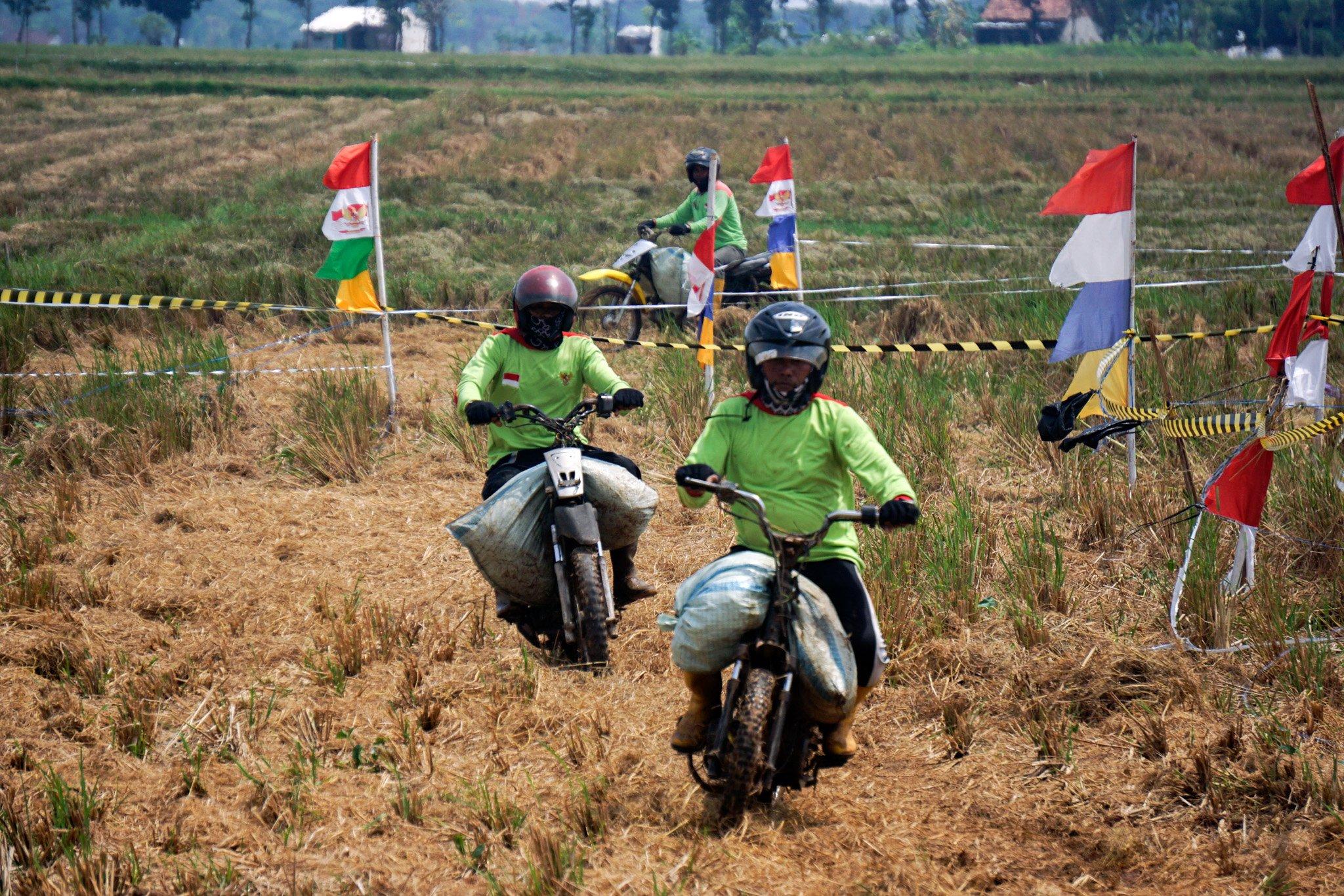 Sejumlah warga mengikuti balap sepeda motor gabah di lahan sawah milik warga di Desa Tegalsari, Kandeman, Kabupaten Batang, Jawa Tengah, Minggu (12/9/2021). Lomba balap sepeda motor gabah yang diikuti oleh 30 warga yang berprofesi sebagai ojek gabah itu dalam rangka syukur atas hasil panen padi yang melimpah. ANTARA FOTO/Harviyan Perdana Putra/wsj.