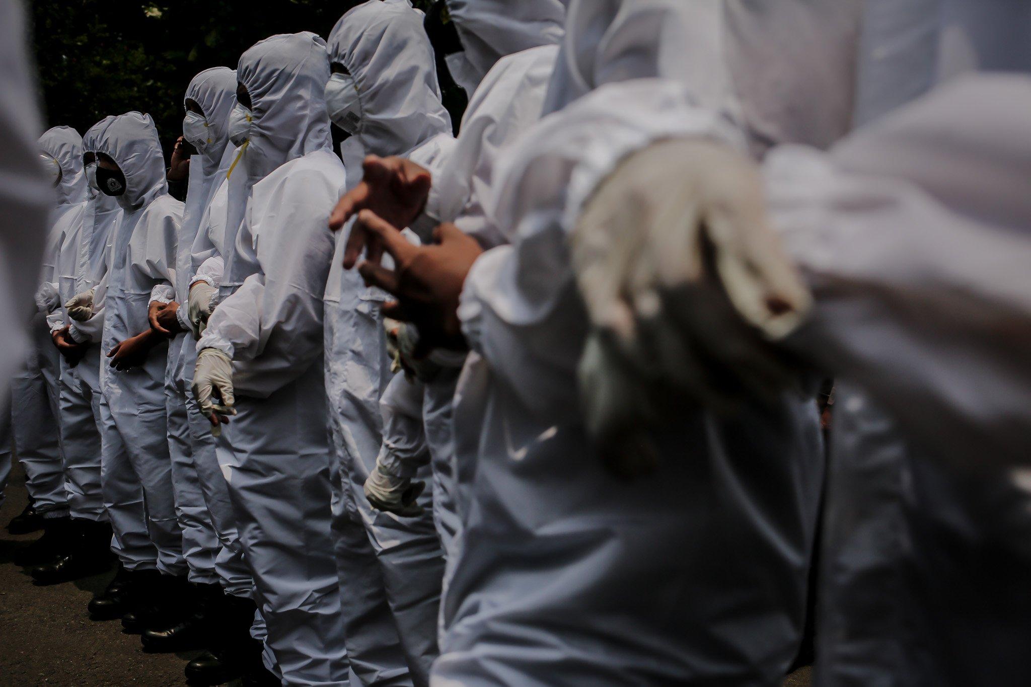 Aparat kepolisian menggunakan Alat Pelindung Diri (APD) berbaris membuat border saat akan membubarkan masa aksi yang digelar Aliansi Mahasiswa Papua( AMP) di Depan Kedutaan Amerika Serikat, Jakarta, Kamis, (30/9/2021).
