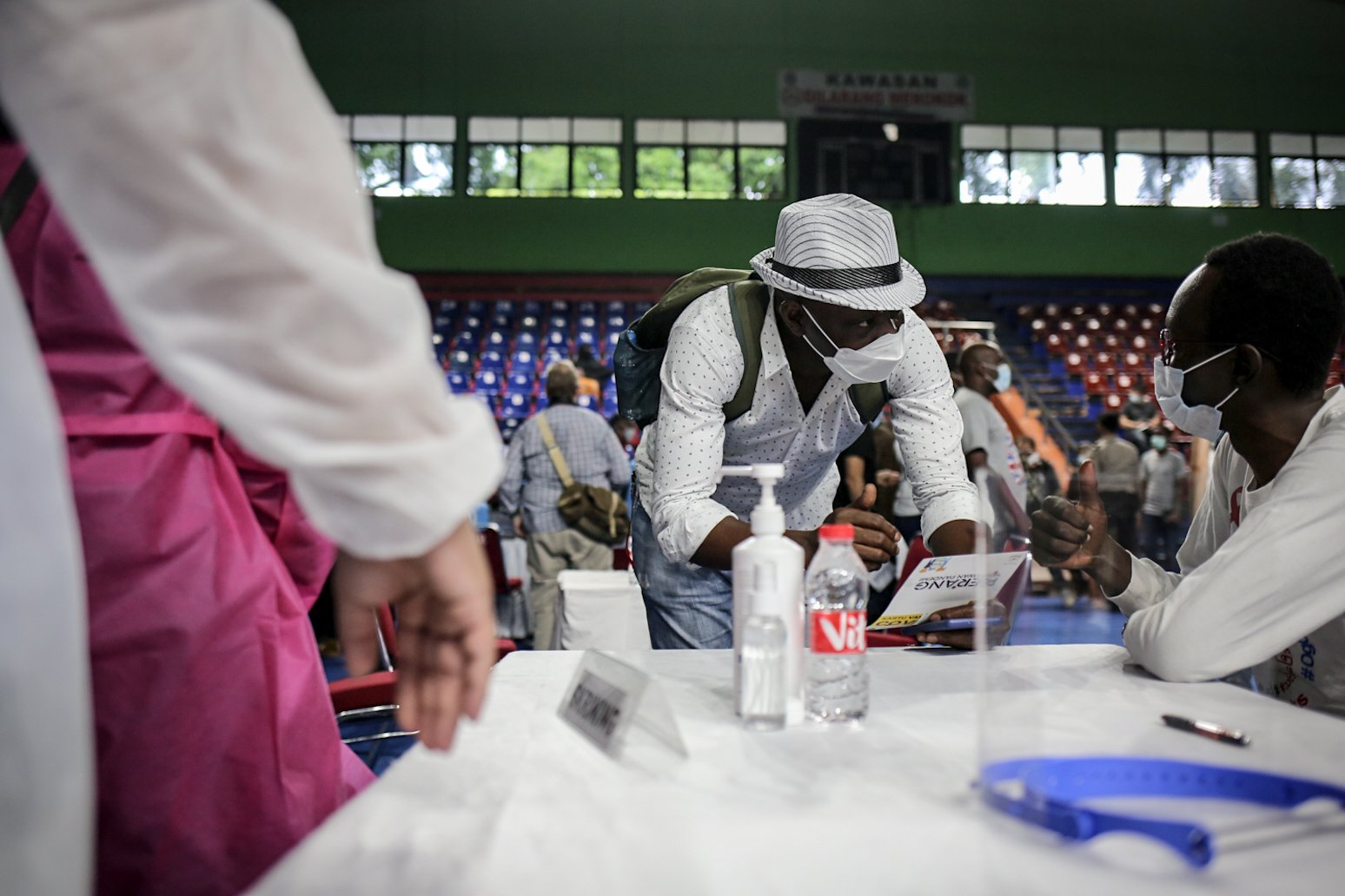 Para pencari suaka menunjukkan kartu identitas saat screening untuk mengikuti vaksinasi COVID-19 di GOR Bulungan, Jakarta Selatan, Kamis (7/10/2021). \r\nVaksinasi tersebut digelar atas kerja sama Pemprov DKI Jakarta, UNHCR dan Kadin Indonesia. \r\nSebanyak 600 vaksin dosis pertama disediakan dalam vaksinasi tersebut.