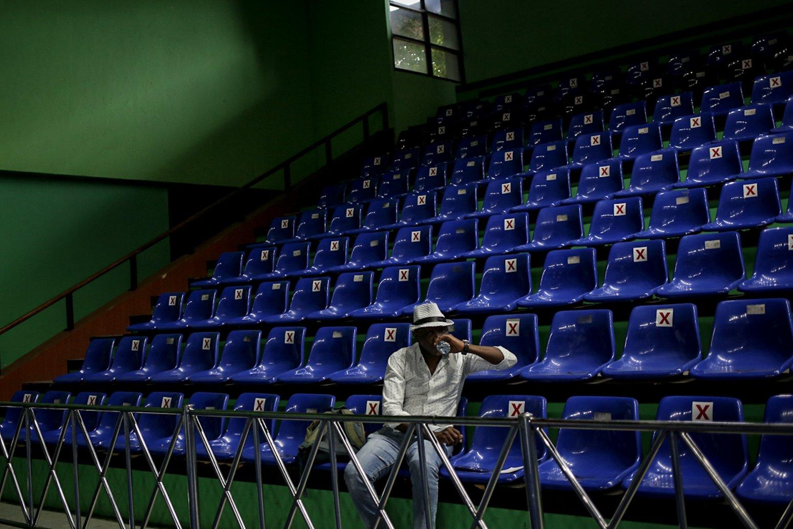 Pencari suaka duduk mengantre saat mengikuti vaksinasi COVID-19 di GOR Bulungan, Jakarta Selatan, Kamis (7/10/2021). Vaksinasi tersebut digelar atas kerja sama Pemprov DKI Jakarta, UNHCR dan Kadin Indonesia. \r\n\r\n