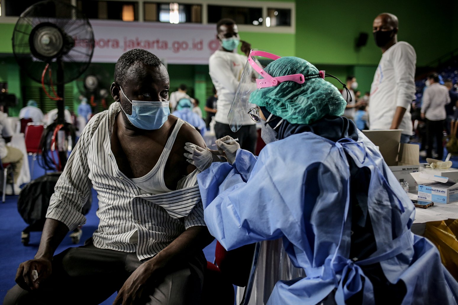 Seorang pencari suaka membuka bajunya saat disuntikkan vaksinasi COVID-19 di GOR Bulungan, Jakarta Selatan, Kamis (7/10/2021). Vaksinasi tersebut digelar atas kerja sama Pemprov DKI Jakarta, UNHCR dan Kadin Indonesia. Sebanyak 600 vaksin dosis pertama disediakan dalam vaksinasi tersebut.
