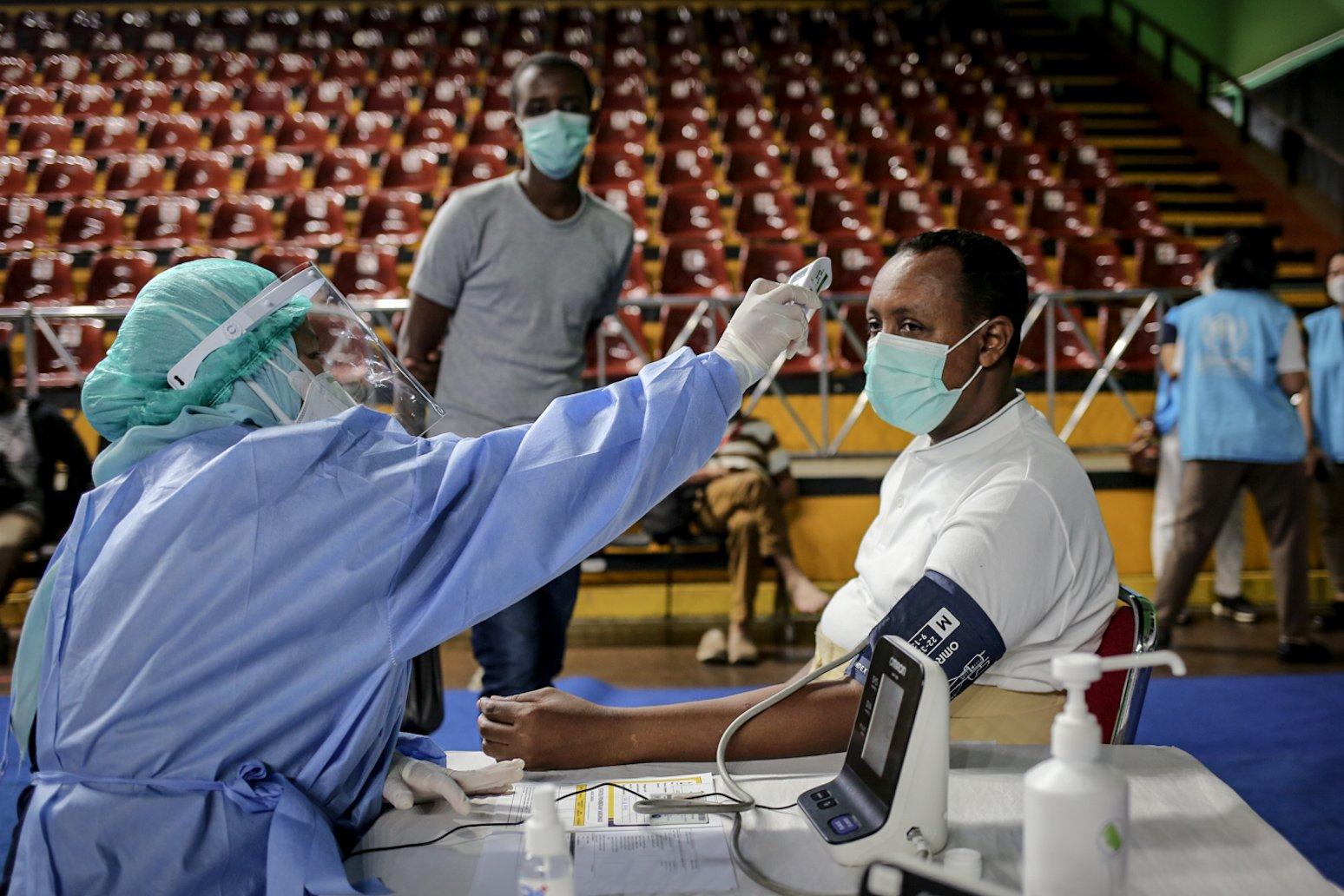 Tenaga medis memeriksa suhu tubuh pencari suaka menggunakan termometer saat vaksinasi COVID-19 di GOR Bulungan, Jakarta Selatan, Kamis (7/10/2021). \r\nVaksinasi tersebut digelar atas kerja sama Pemprov DKI Jakarta, UNHCR dan Kadin Indonesia. \r\nSebanyak 600 vaksin dosis pertama disediakan dalam vaksinasi tersebut.