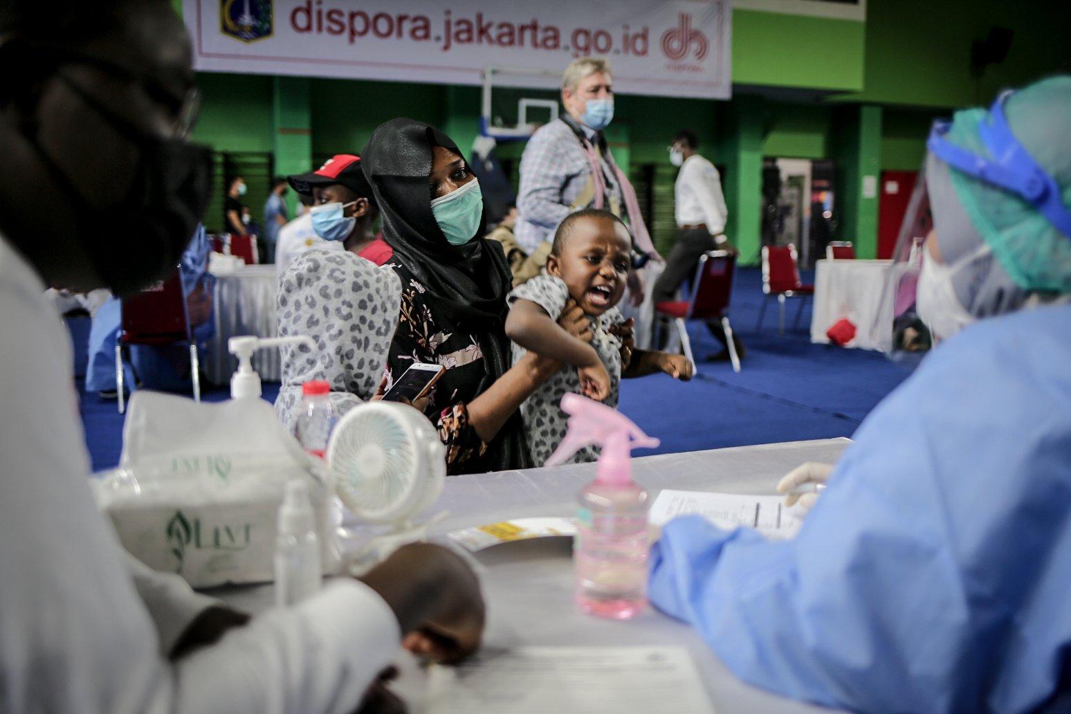 Para pencari suaka menggendong anaknya saat mengikuti vaksinasi COVID-19 di GOR Bulungan, Jakarta Selatan, Kamis (7/10/2021). \r\nVaksinasi tersebut digelar atas kerja sama Pemprov DKI Jakarta, UNHCR dan Kadin Indonesia. \r\nSebanyak 600 vaksin dosis pertama disediakan dalam vaksinasi tersebut.