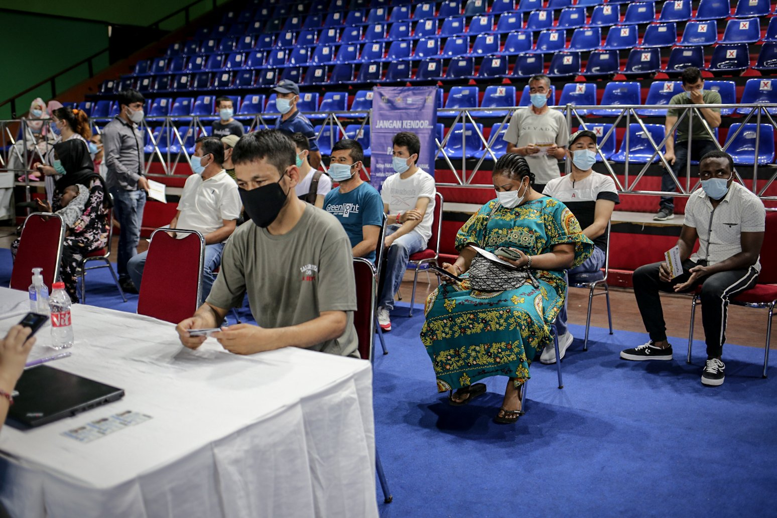 Pencari suaka berbaris antre melakukan skrining untuk mengikuti vaksinasi COVID-19 di GOR Bulungan, Jakarta Selatan, Kamis (7/10/2021). \r\nVaksinasi tersebut digelar atas kerja sama Pemprov DKI Jakarta, UNHCR dan Kadin Indonesia. \r\nSebanyak 600 vaksin dosis pertama disediakan dalam vaksinasi tersebut.
