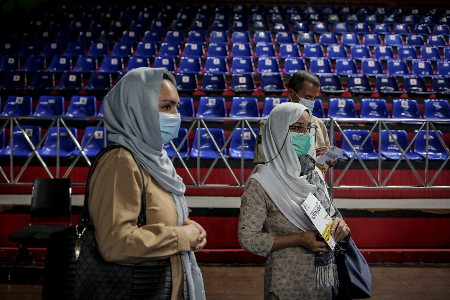 Pencari suaka berbaris antre saat mengikuti vaksinasi COVID-19 di GOR Bulungan, Jakarta Selatan, Kamis (7/10/2021). \r\nVaksinasi tersebut digelar atas kerja sama Pemprov DKI Jakarta, UNHCR dan Kadin Indonesia. \r\nSebanyak 600 vaksin dosis pertama disediakan dalam vaksinasi tersebut.