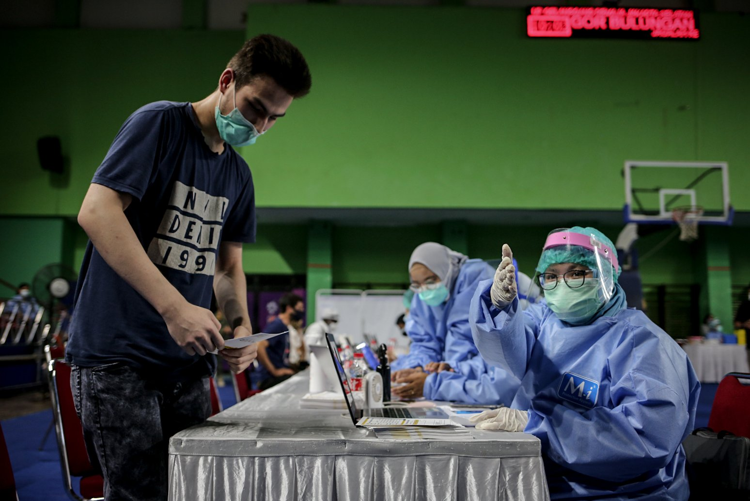 Petugas medis mengarahkan pencari suaka saat vaksinasi COVID-19 di GOR Bulungan, Jakarta Selatan, Kamis (7/10/2021). Vaksinasi tersebut digelar atas kerja sama Pemprov DKI Jakarta, UNHCR dan Kadin Indonesia. Sebanyak 600 vaksin dosis pertama disediakan dalam vaksinasi tersebut.