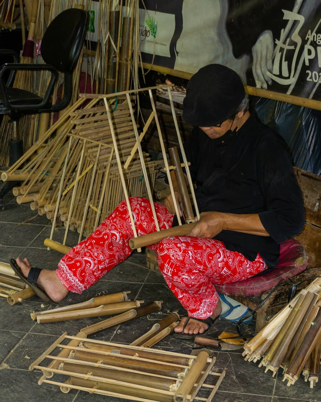 Pengrajin angklung sedang membuat angklung