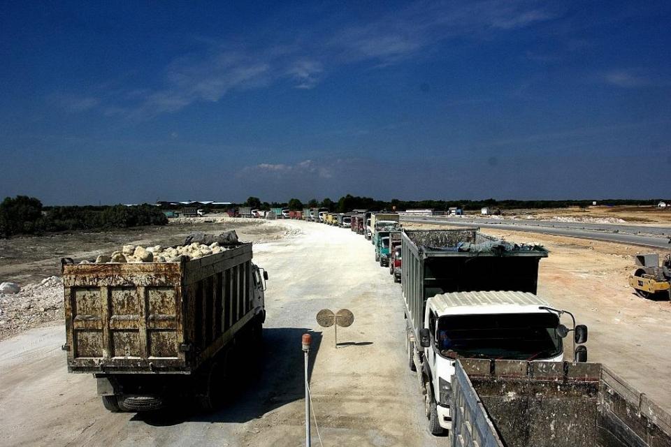 Antrean truk pengangkut batu dalam proses konstruksi kawasan industri terintegrasi Java Integrated Industrial and Port Estate (JIIPE) di Gresik, Jawa Timur.