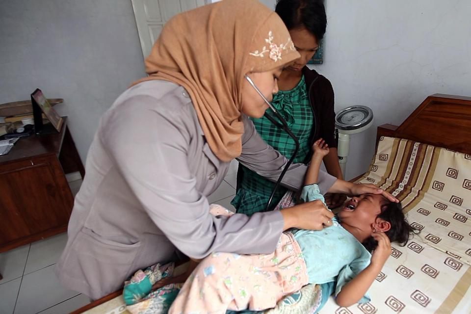 Petugas kesehatan desa sedang memeriksa bayi.