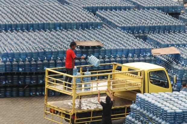 Pekerja menukar galon air kemasan yang kosong dengan baru di kawasan kalibata, Jakarta Selatan, Selasa (25/2). Saat ini total pasar air minum dalam kemasan (AMDK) di Indonesia mencapai 20 miliar liter air dengan pertumbuhan 12 persen per tahun.