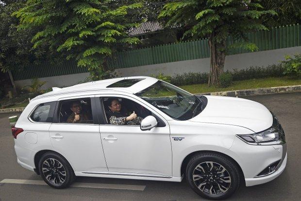 Menteri Perindustrian Airlangga Hartarto (kanan) mencoba kendaraan listrik Mitsubishi Outlander PHEV usai serah terima di Jakarta, Senin (26/2). Mitsubishi Motors memberikan delapan mobil listrik Mitsubishi Outlander PHEV dan dua i-MiEV serta empat unit q