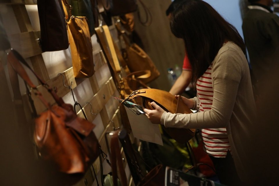 Seorang pengunjung sedang melihat-lihat produk kerajinan kulit di pameran perdagangan