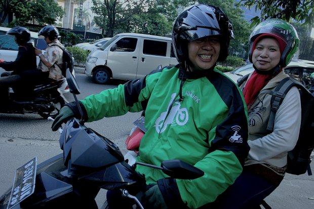 Pengemudi ojek Go-Jek mengantarkan penumpang menuju salah satu kawasan perkantoran di Jakarta, Jumat (26/06/2015).