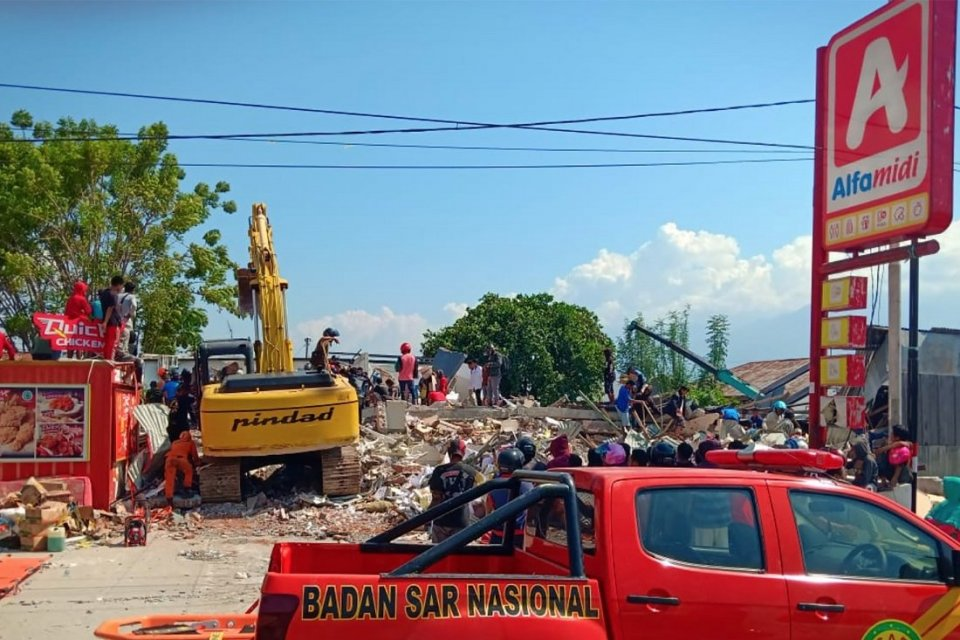 Warga mengambil makanan dari minimarket yang ambruk di Palu, Sulawesi Tengah, Minggu (30/9). Warga diperkirakan terpaksa mengambil makanan lantaran te