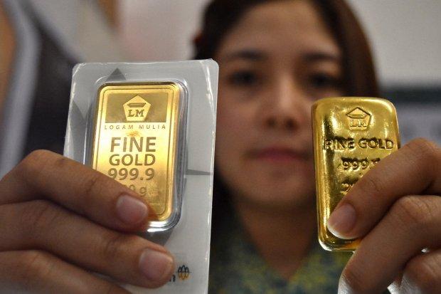 Petugas menunjukkan imitasi emas logam mulia produk PT Aneka Tambang (Antam) yang dipamerkan di gerai Antam dalam sebuah pameran di Ungaran, Kabupaten Semarang, Jawa Tengah, Minggu (9/9).