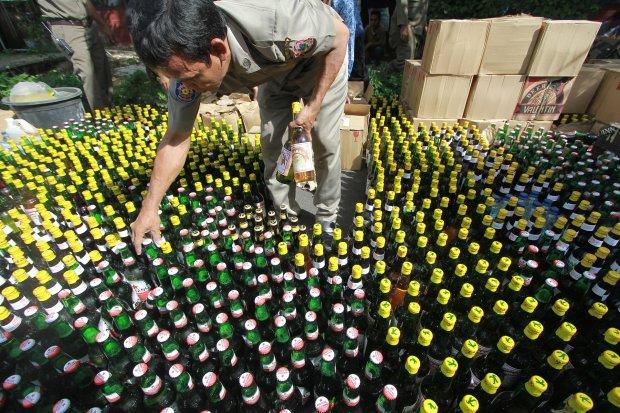 Petugas Satuan Polisi Pamong Praja (Satpol PP) menata botol berisi minuman keras yang akan dimusnahkan di kantor Bupati Gorontalo, Kabupaten Gorontalo, Gorontalo.