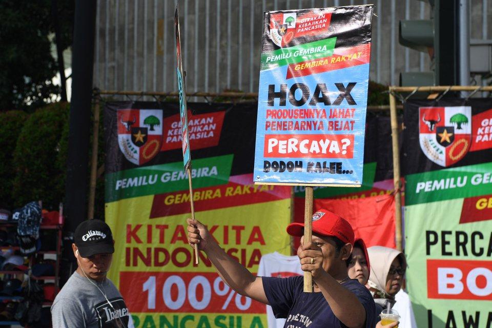 Warga mengangkat poster bertulis penolakan terhadap hoaks jelang Pemilu 2019 saat Hari Bebas Kendaraan Bermotor di kawasan Bundaran HI, Jakarta, Minggu (3/2/2019). Aksi tolak hoaks tersebut digelar untuk mewujudkan pesta demokrasi yang aman dan damai.