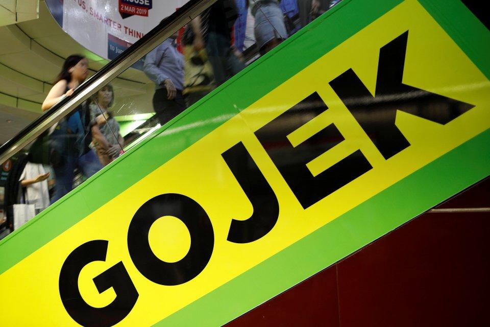 Komuter melewati iklan Gojek di Singapura, Senin (4/3/2019).