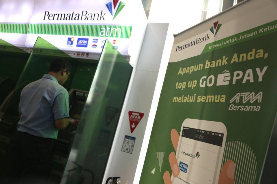 Seorang nasabah bertransaksi di ATM PT Bank Permata Tbk, kawasanWorld Trade Center 2, Sudirman, Jakarta Selatan (18/3).