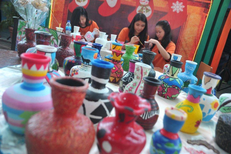 Siswa melukis kendi tanah liat pada Pasar Seni Kreatif Siswa di Perguruan Methodist 2 Palembang,Sumsel, Kamis (19/1). Pameran yang diikuti siswa taman kanak-kanak hingga SMU ini memajang hasil karya seni buatan siswa.