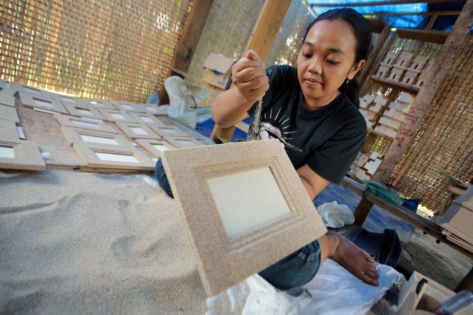 Perajin menyelesaikan kerajinan bingkai berbahan pasir pantai di salah satu sentra di Pagu Kediri, Jawa Timur, Selasa (10/10). Badan Ekonomi Kreatif (Bekraf) menargetkan pendapatan industri kreatif nasional sepanjang 2017 bisa mencapai Rp1.000 triliun den