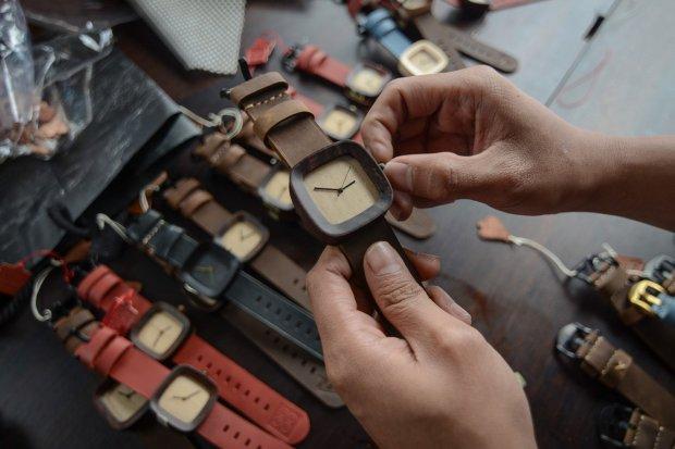 Pekerja mengatur waktu jam tangan yang terbuat dari kayu di Cipadung, Bandung, Jawa Barat, Rabu (28/2).