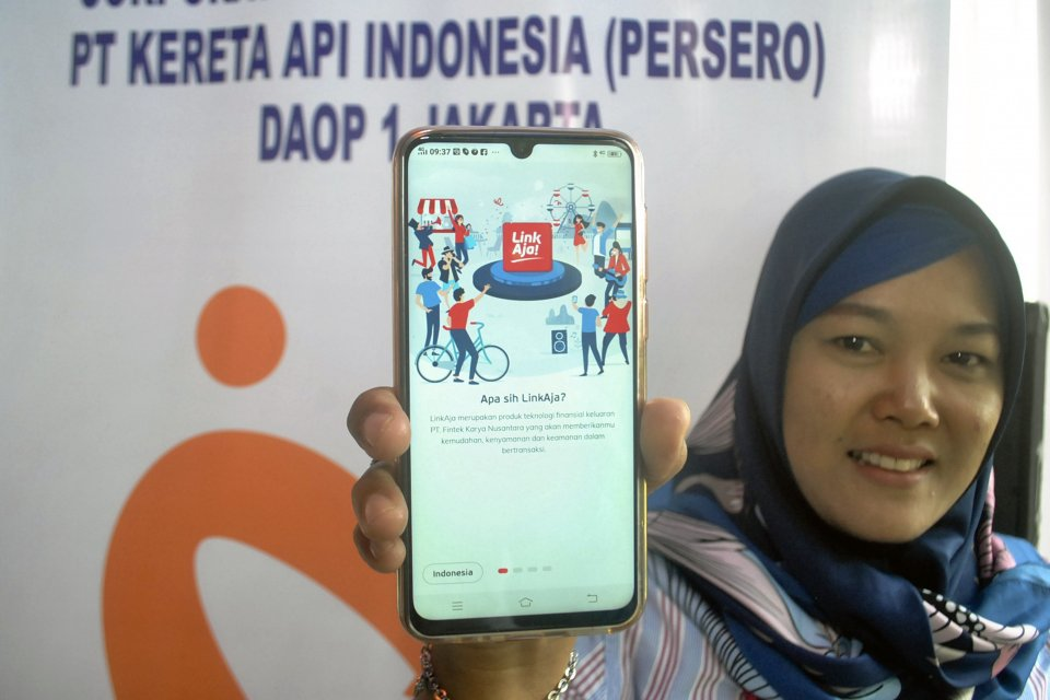 Warga menunjukkan aplikasi pembayaran digital (uang elektronik) LinkAja saat sosialisasi di Stasiun Bogor, Jawa Barat, Selasa (2/4/2019). Sistem pembayaran digital LinkAja yang merupakan bentukan tujuh BUMN (Telkomsel, BRI, BNI, BTN, Bank Mandiri, Pertami