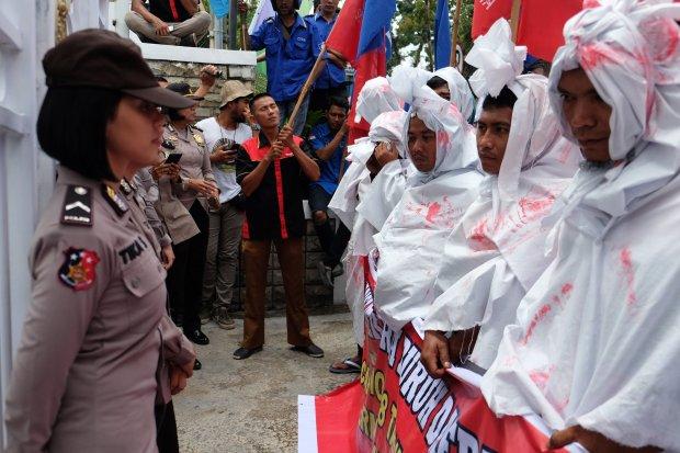 """Sejumlah buruh yang tergabung dalam Aliansi Pekerja Buruh Daerah Sumut (APBD-SU) berunjuk rasa dengan memakai kain """"ala pocong"""" jelang peringatan Hari Buruh Internasional, di depan Kantor Gubernur Sumatera Utara, Medan, Selasa (30/4/2019). Mereka me"""