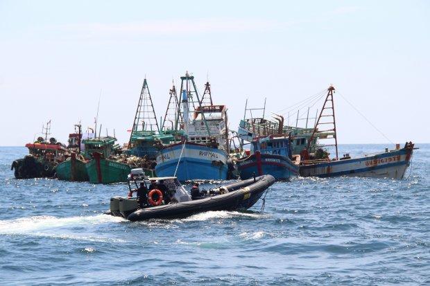 Kapal patroli TNI AL melintasi belasan kapal nelayan Vietnam sesaat sebelum ditenggelamkan di Pulau Datuk, Kabupaten Mempawah, Kalimantan Barat, Sabtu (4/5/2019). Kementerian Kelautan dan Perikanan menenggelamkan 13 dari 51 kapal nelayan asing asal Vietna