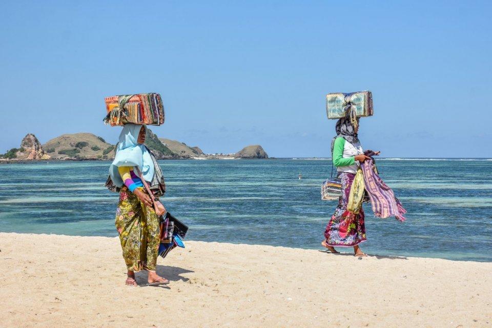 Sejumlah pedagang kain tenun melintas di kawasan wisata Kuta Beach Park The Mandalika di Desa Kuta, Kecamatan Pujut, Praya, Lombok Tengah, NTB, Jumat (17/5/2019). Pemerintah menargetkan kunjungan wisatawan ke NTB pada 2019 sebanyak 4 juta wisatawan yang t