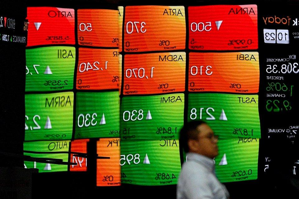 Karyawan melintas di depan layar pergerakan Indeks Harga Saham Gabungan (IHSG), Bursa Efek Indonesia, Jakarta. IHSG hari ini, Senin (12/8) terkoreksi 0,53% pada akhir sesi I perdagangan. Koreksi IHSG didorong oleh penurunan pada sektor finansial, konsumer